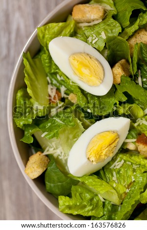 Caesar salad with eggs, lettuce, croutons and parmesan - stock photo