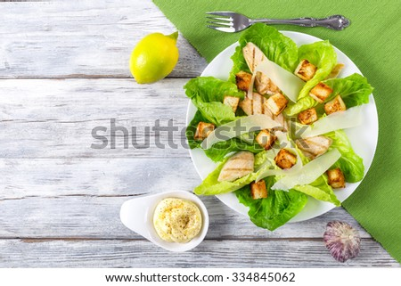 Caesar Salad with grilled chicken and parmesan cheese on the white dish on the old wooden table, view from above - stock photo
