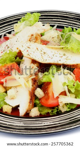 Caesar Salad with Grilled Chicken Breast, Garlic Crouton, Lettuce, Tomatoes and Grated Parmesan Cheese on Striped Plate closeup on white background - stock photo