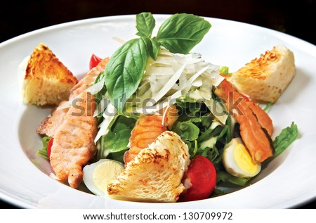 Caesar salad with salmon. Fried salmon, light-green mix, quail eggs, cherry tomatoes, Parmezan cheese & Caesar sauce - stock photo