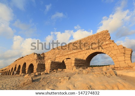 Caesarea aqueduct beach at sunset - stock photo