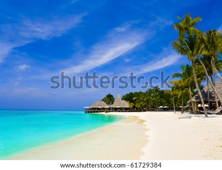 Cafe and palms on a tropical beach - travel background - stock photo