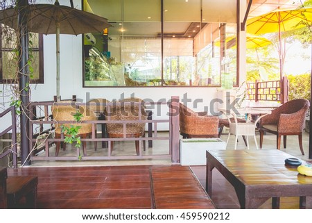 Cafe new and luxury with sunny morning in Bangkok, Thailand. Chairs at the relax corner inside the coffee shop.