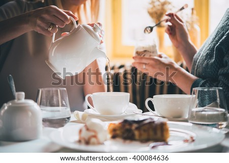 Cafe or bar table with desserts and tea. Two people talking on background. Toned picture - stock photo