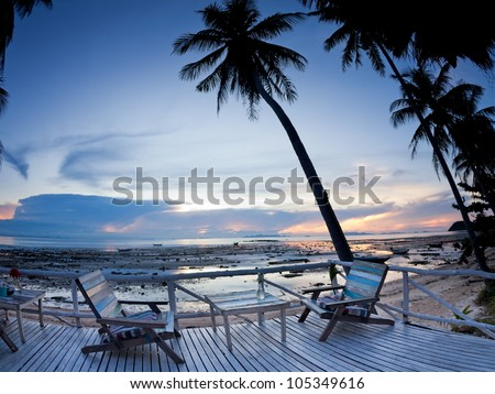 Cafe outdoor with terrace on sunset beach with palm tree - stock photo
