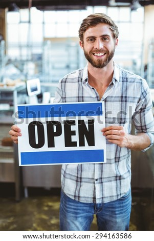 Cafe owner smiling at the camera holding an open sign - stock photo