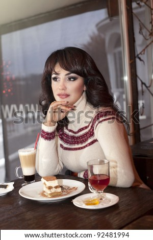 Cafe Pretty italian woman sitting in cafe restaurant thinking looking out the window drinking coffee cup of tea cocktail eating tasty dessert  cheesecake tiramisu - stock photo