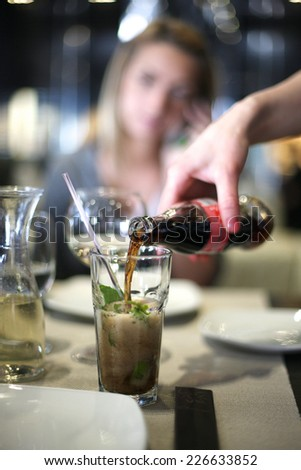 Cafe service, waitress hand pouring beverage