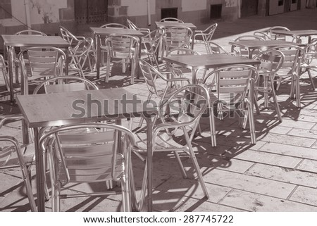 Cafe Table and Chairs in Outdoor Setting in Black and White Sepia Tone - stock photo
