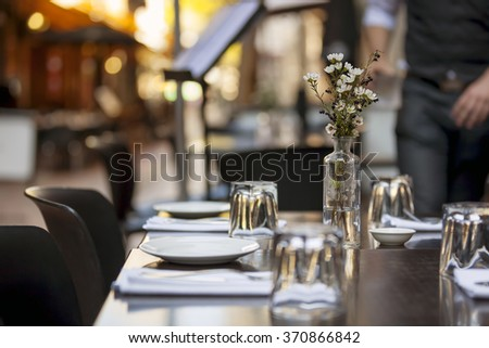 Cafe table in laneway.  Focus on Flowers.   - stock photo