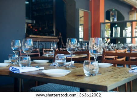 Cafe table setting with glasses and plates - stock photo