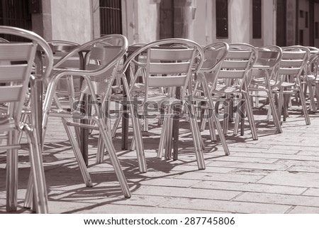 Cafe Tables and Chairs in Outdoor Setting in Black and White Sepia Tone - stock photo