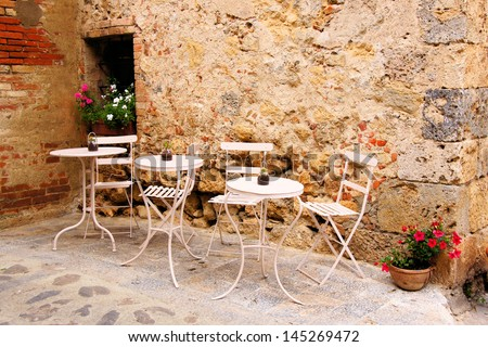 Cafe tables and chairs outside in a quaint corner of Tuscany, Italy - stock photo