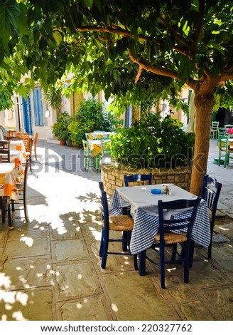 Cafe tables under tree. Vourliotes -Samos island, Greece - stock photo