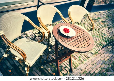 Cafe terrace in small European city at summer day - stock photo