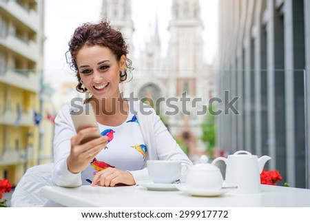 Cafe with wifi. Young attractive smiling woman using smart phone while drinking tea at sidewalk restaurant. - stock photo