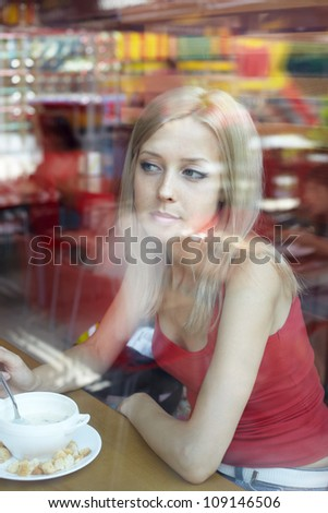 Cafe. Woman at cafe thinking looking out the window eating. - stock photo