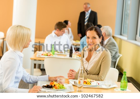 Cafeteria lunch young business women eat salad at office canteen - stock photo