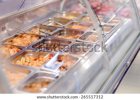 Cafeteria take-out food in showcase window - Image of cooked snack bar meals in trays at display  - stock photo
