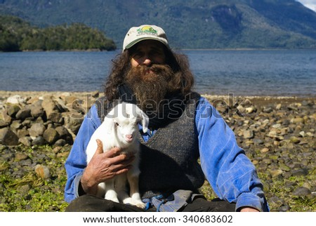 Cagalandia, Chile - Circa October 2008: Old bearded man with cap poses with his little white lamb near lake in Chile.
