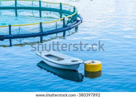 Cages for fish farming and the boat - stock photo