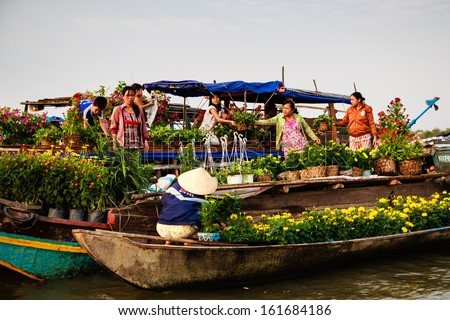 CAI BE TOWN, TIEN GIANG PROVINCE, VIETNAM - FEB 02: Flower vendors on their boats at Cai Be Floating Market on February 02, 2013. Cai Be Market is one of most famous floating market in Vietnam. - stock photo