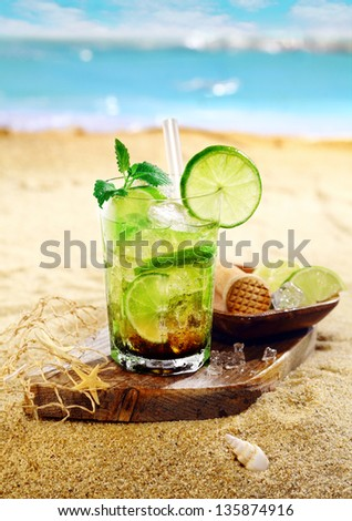 Caipirinha Rum and lime cocktail garnished with mint leaves and served on a wooden board on the golden sand of a tropical beach - stock photo