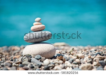 Cairn on the background of the sea, the beach and the sand. The background image for the screen saver, or for philosophical or psychological information and advertising concepts. Pyramid - balance.