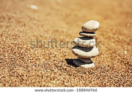 Cairn (pile from stones) on the beach sand near sea, harmony and stability concept - stock photo