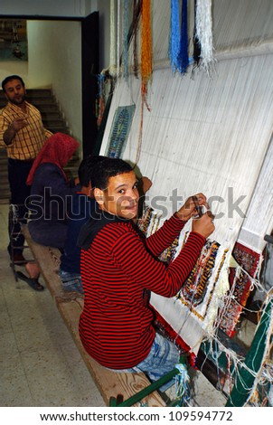 CAIRO EGYPT NOVEMBER 26: Unknown child weaving rugs on November 26 2008 in Cairo Egypt.  childhood in which school is replaced by a factory and learning weaving rugs from light till dark. - stock photo
