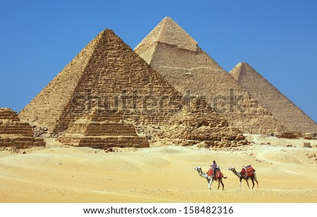 CAIRO - JULY 3: The pyramids at Giza near Cairo, Egypt on July 3, 2010. The Great Pyramid of Khufu is the only one of the Seven Wonders of the Ancient World still in existence. - stock photo