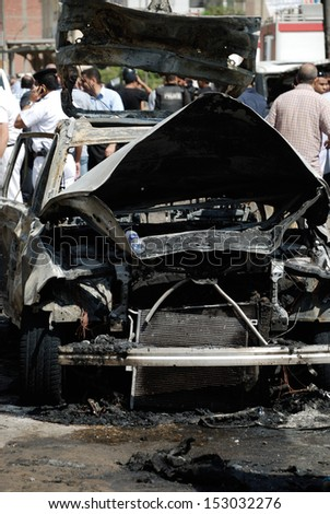 CAIRO - SEP 05: Demonstration one of the exploded cars belongs to the interior minister's convoy after the explosion that was targeting Minister in Mostafa Nahas st. Cairo, Egypt on September 05, 2013 - stock photo