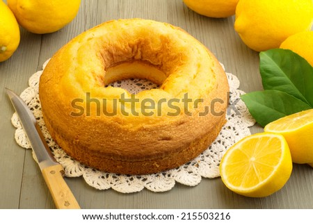cake and yellow lemons on wooden board - stock photo