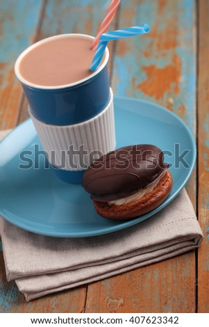 Cake Bouchee and hot chocolate on a rustic table - stock photo