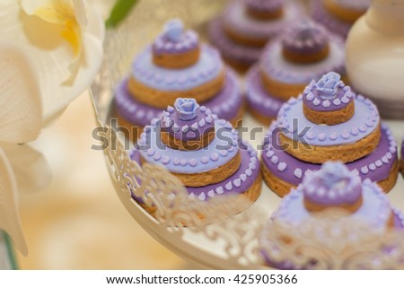 Cake, candies, marshmallows, cake, fruits and other sweets on dessert table. Violet and White Colors. - stock photo