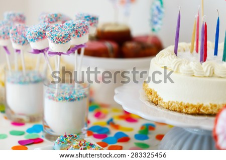Cake, candies, marshmallows, cakepops, fruits and other sweets on dessert table at kids birthday party - stock photo