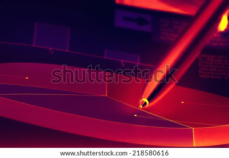 Cake diagram with pencil pointing in infrared light on dark background  - stock photo