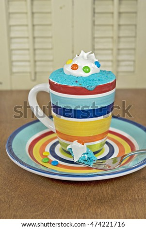 cake in striped mug with whipped cream and colorful candy