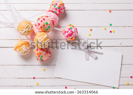 Cake pops  and empty tag on white wooden background. Selective focus.Place for text. - stock photo