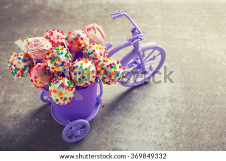 Cake pops  in decorative bicycle on grey slate  background. Selective focus. Toned image. - stock photo