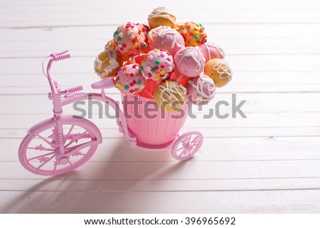 Cake pops  in decorative  pink bicycle on white wooden background. Selective focus. - stock photo
