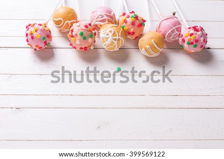 Cake pops on white  painted wooden background. Selective focus.Place for text.