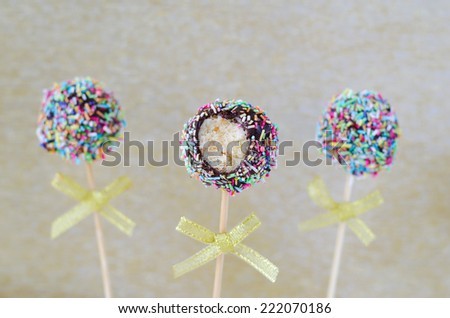 Cake pops with colorful sprinkles and bitten off piece   - stock photo
