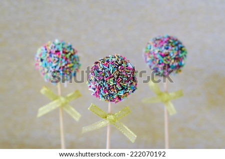 Cake pops with colorful sprinkles on golden background  - stock photo