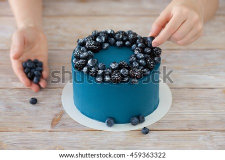 Cake with blue cream for men, decorated with blackberry and blueberry. Hands of Chef decorate the cake with berries. Selective focus. - stock photo