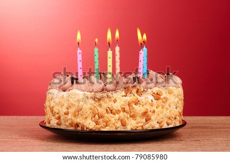 Cake with candles on red background - stock photo