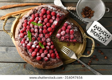 Cake with Chocolate Glaze and raspberries on wooden background - stock photo