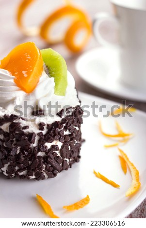 cake with cream, chocolate crumb, slices of tropical fruits and orange skin  on white plate, macro shot