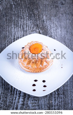 Cake with dry apricot and sugar powder on the white plate on wooden table. Selective focus. Toned. - stock photo