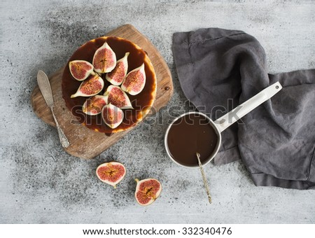Cake with fresh figs and salted caramel on wooden serving board over grunge background, top view - stock photo